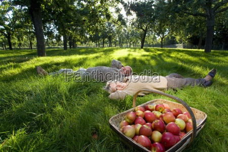 mature couple lying on grass by