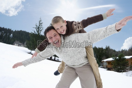 father and son playing in winter