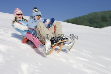 brother and sister sledding downhill
