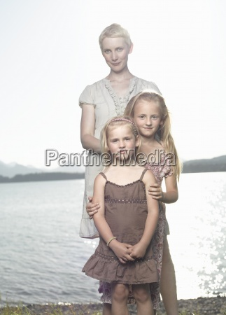a mother and two daughters standing