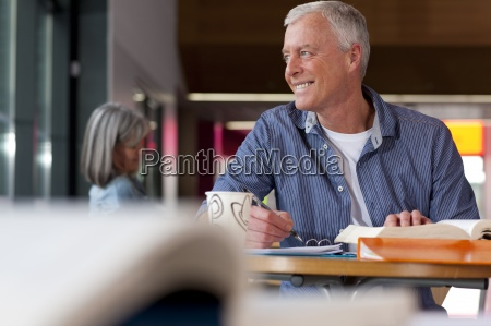 smiling mature student thinking and sitting