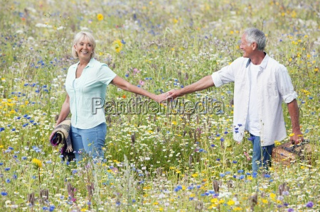 smiling senior couple holding hands and