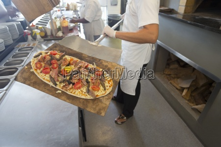 chef holding pizza on spatula in