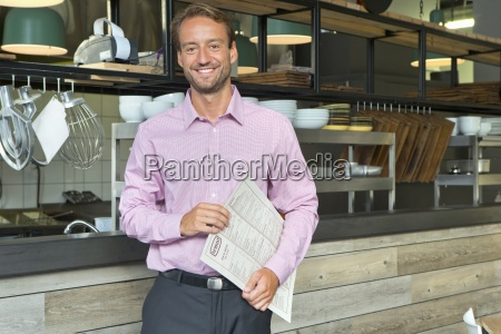 smiling business owner holding menu in