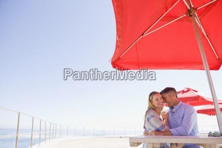 smiling couple hugging under umbrella at