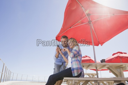 smiling couple using cell phone under