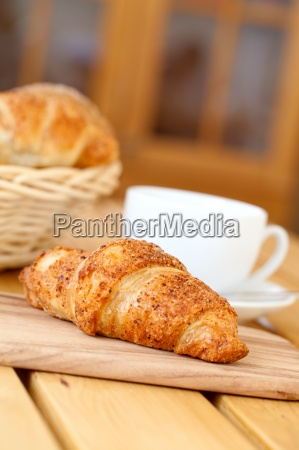fresh croissant and white cup coffee