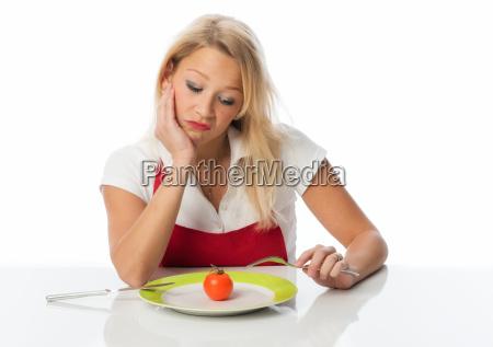 frau starrt auf eine tomate und