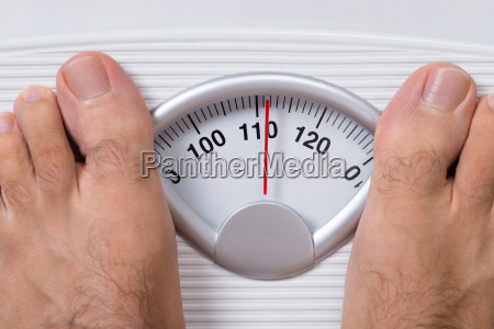 mans feet on weight scale