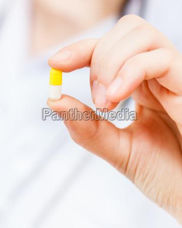 krankenschwester haelt pilule in finger