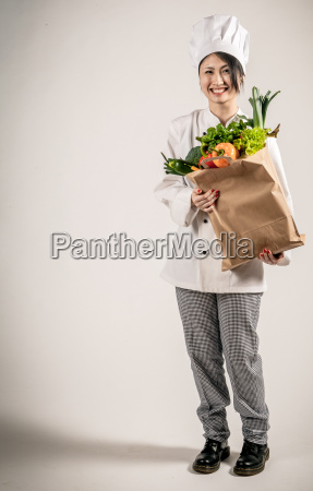 happy chef holding paper bag with