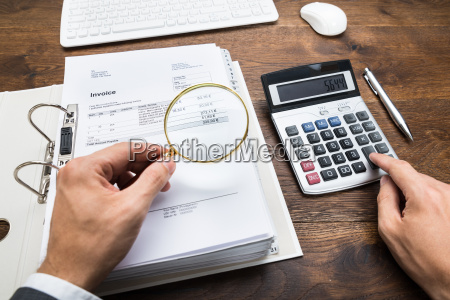 businessperson examining bills with magnifying glass