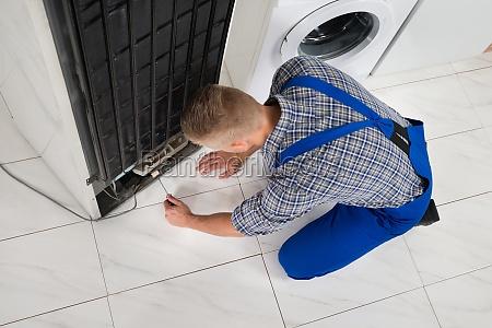 repairman making refrigerator appliance