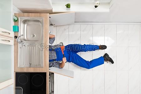 worker lying on floor repairing sink