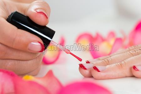 female hands applying nail varnish