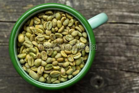 unroasted coffee beans in mug