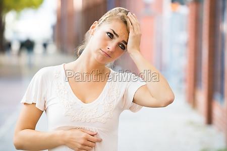 woman massaging head on street
