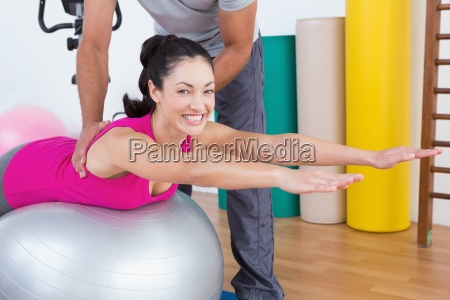 trainer with smiling woman on exercise