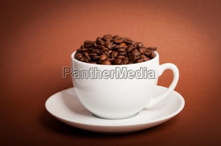 kaffeebohnen in der tasse auf braunem