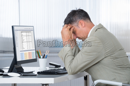 accountant suffering from headache at desk