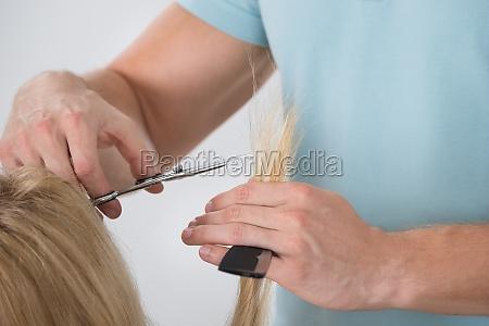woman having her hair cut by