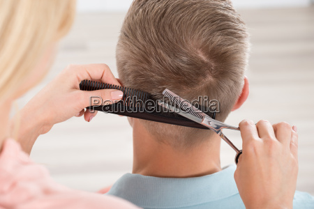 man getting haircut from female hairdresser