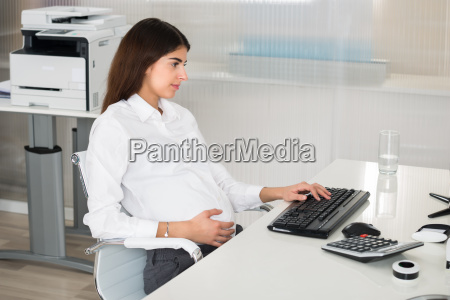 pregnant businesswoman using computer at desk