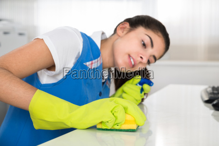 janitor cleaning desk with sponge at