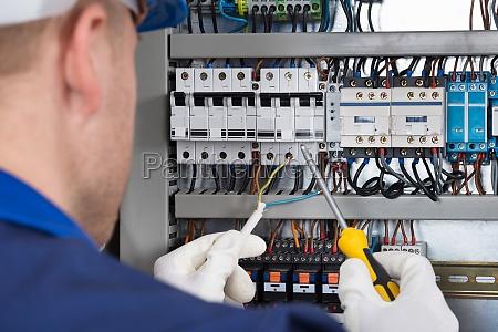 male technician checking fusebox