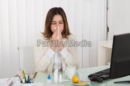 businesswoman blowing her nose