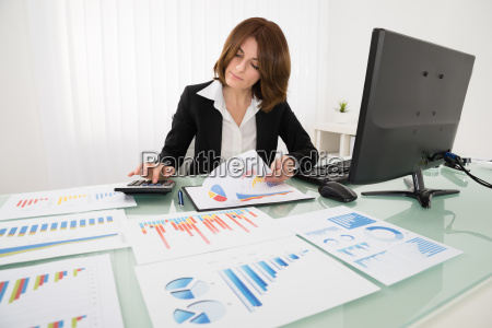young businesswoman analyzing report on chart