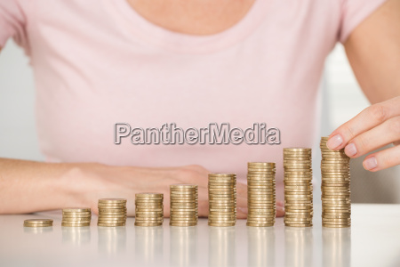 woman stacking coins at desk
