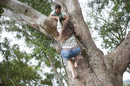 teenager helping his girlfriend climing up