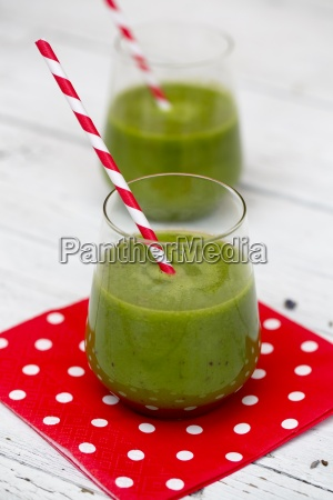 glass of green smoothie with drinking