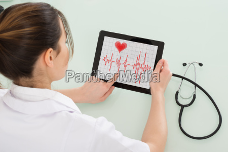 female cardiologist analyzing heartbeat on digital