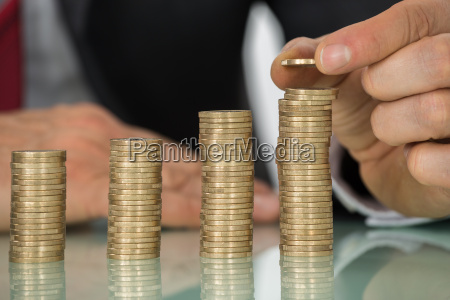 businessman placing coin over stack of