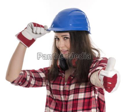 weiblicher handwerker mit helm zeigt daumen