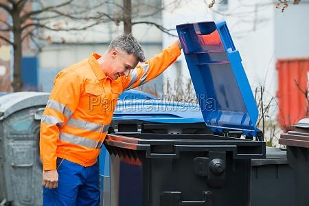 man looking in dustbin on street
