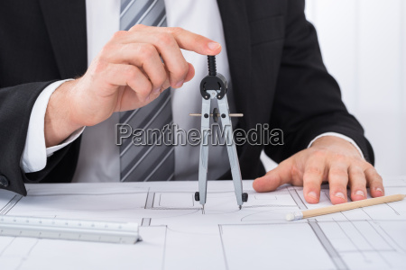 male architect hands holding compass on