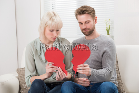 couple holding red broken heart