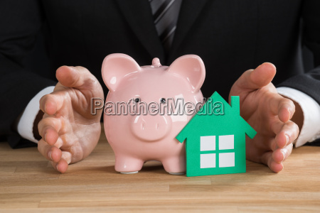 businessman protecting green paper house and