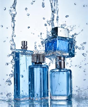 four perfume bottles under flowing water