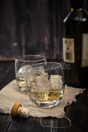two tumblers with whisky and ice