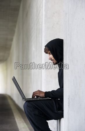 hacker with laptop sitting in an
