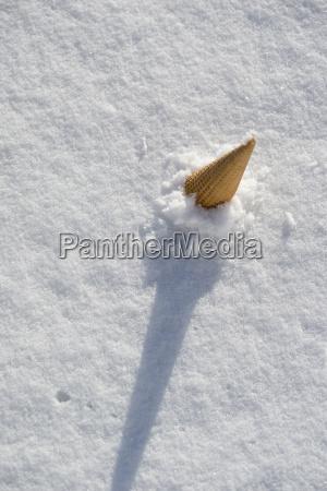 ice cream cone sticking in snow
