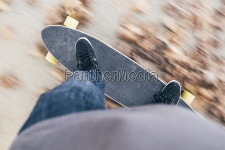 junger mann faehrt longboard