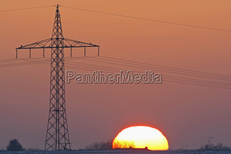 germany sunset besides electricity pylon