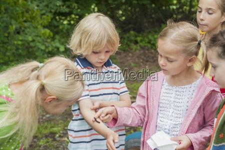 germany children watching caterpillar of peackock