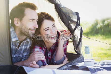 smiling couple peering from inside tent