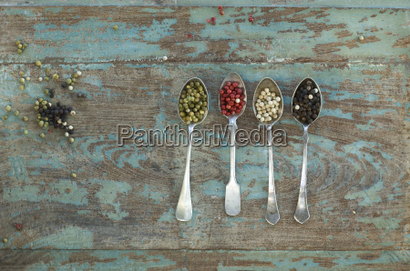 row of four silver spoons with